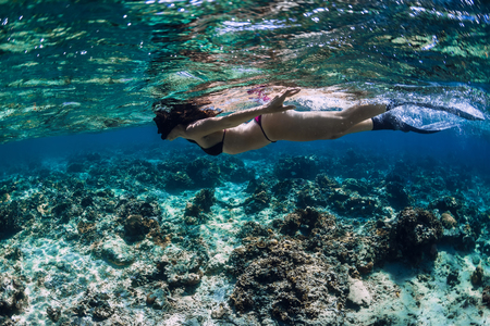 Woman freediver glides with fins over coral reef. 写真素材