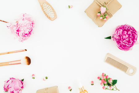 Beauty frame composition of pink peony with hairbrush, tassel and gift box on white background. Flat lay, top view 写真素材