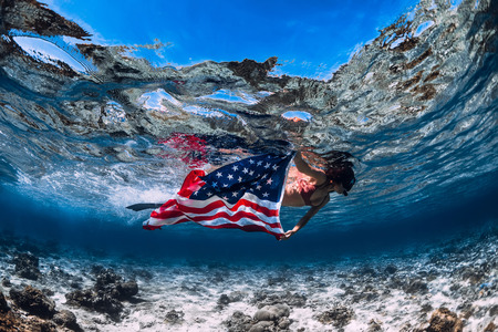 Beautiful girl freediver swim over sandy sea bottom with United States flag. Independence day.