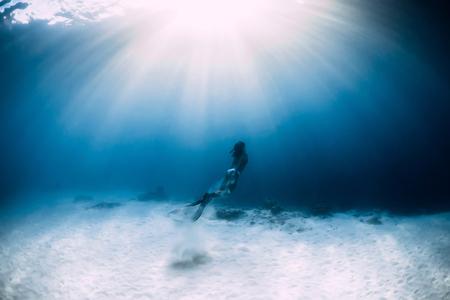 Woman freediver in bikini over sandy sea with fins. Freediving underwater in blue ocean