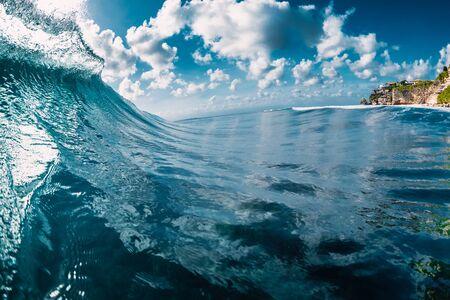 Blue barrel wave in ocean. Breaking wave and sun light
