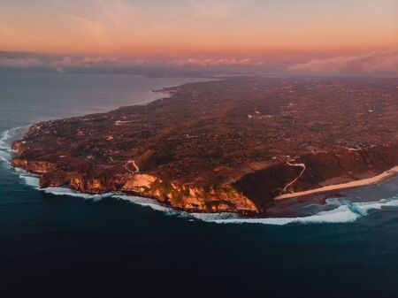 Aerial view of rocky shore with cliff and ocean warm sunset. Uluwatu, Bali 写真素材