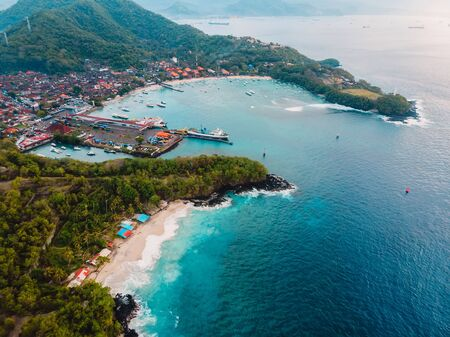 Tropical beach and village with port, ship and blue ocean. Aerial view