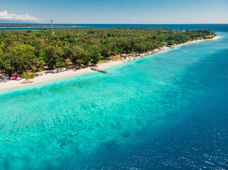 Tropical beach with white sand and turquoise ocean. Aerial view. Paradise holiday resort