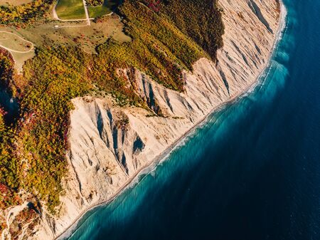 Aerial view of rocky shore with cliff and blue sea