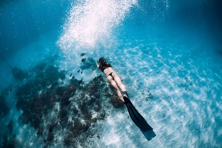 Attractive woman freediver with fins. Free diving underwater in Hawaii