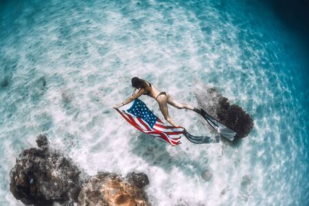 Beautiful woman freediver glides over sandy sea bottom with United States flag. Independence day.