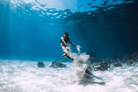 Woman freediver with white sand glides over sandy sea with fins. Freediving underwater in Hawaii