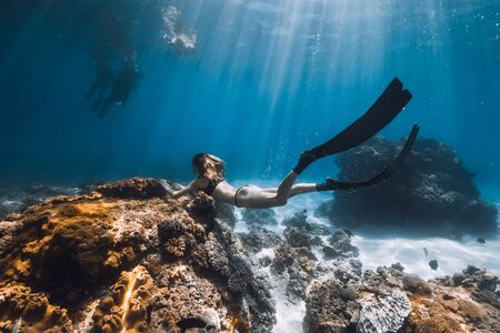 Woman freediver glides with fins and corals. Freediving underwater in blue ocean 写真素材