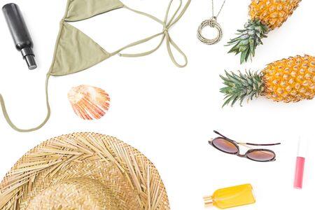 Summer frame with pineapple, sun glasses, straw hat and bikini swimwear on white 写真素材