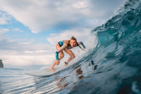 Beautiful surfer girl on surfboard. Woman in ocean during surfing. Surfer and barrel wave