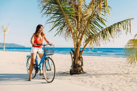Happy young woman on blue bicycle near ocean in tropical island