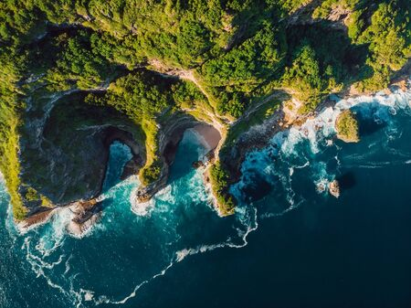 Amazing cliff, rocks and blue ocean with waves in Bali. Aerial view