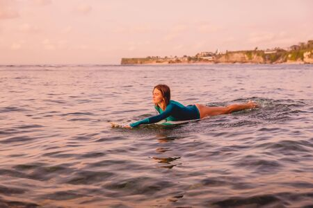 Surf girl with perfect body on surfboard in ocean. Surfing at sunset time Stock Photo