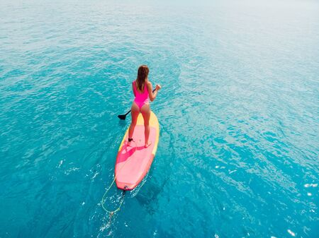 Aerial view of woman on stand up paddle board in ocean.