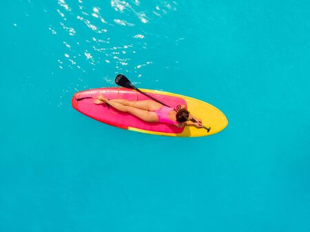 Woman relax on stand up paddle board on a quiet blue ocean