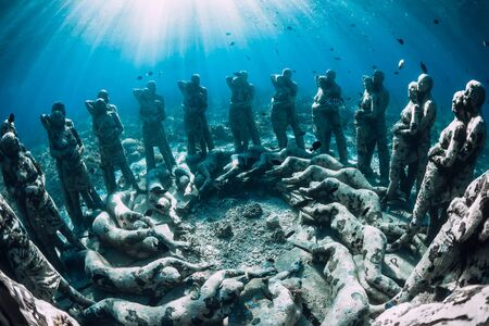 Underwater statues in blue ocean with fish. Underwater tourism in ocean.