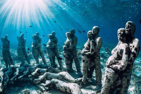 Underwater statues in blue ocean with fish. Underwater tourism in ocean. Stock Photo