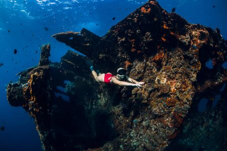 Woman freediver glides with fins at wreck ship. Freediving in blue ocean near wreck Stock Photo