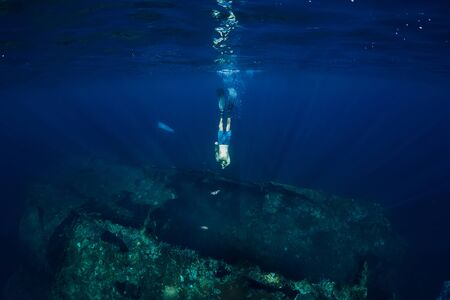 Freediver man dive underwater at shipwreck. Freediving in ocean
