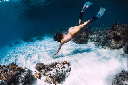 Woman freediver dive with fins near corals. Freediving underwater in blue ocean