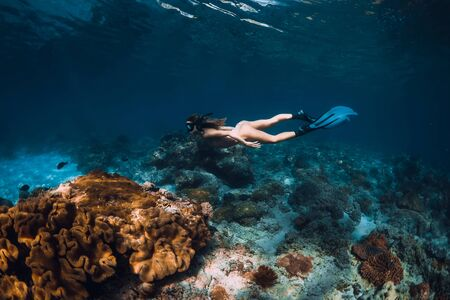 Freediver slim woman with fins glides over coral bottom in underwater Stock Photo