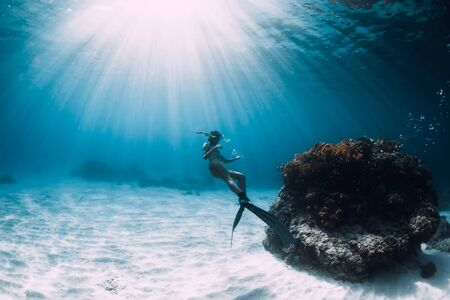 Freediver young woman with fins glides over sandy bottom underwater ocean