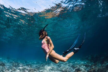 Woman freediver swim in pink swimsuit underwater with fins. Freediving underwater in blue ocean