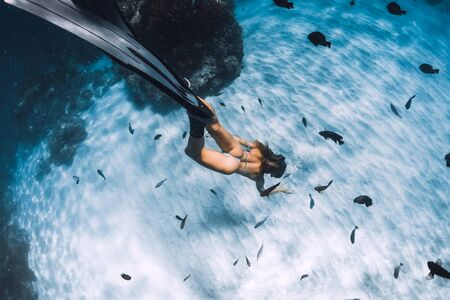 Young woman freediver with fins dive over sandy sea with fishes