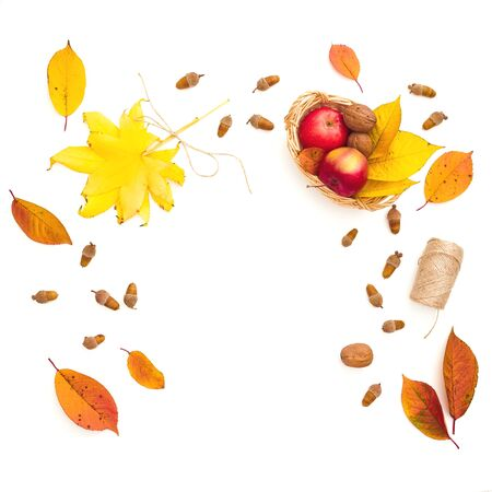 Autumnal composition. Fall leaves, apple, acorns and twine on white background. Thanksgiving concept. Flat lay, top view