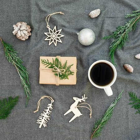 Christmas decoration, evergreen branches, coffee cup and gift box on plaid.