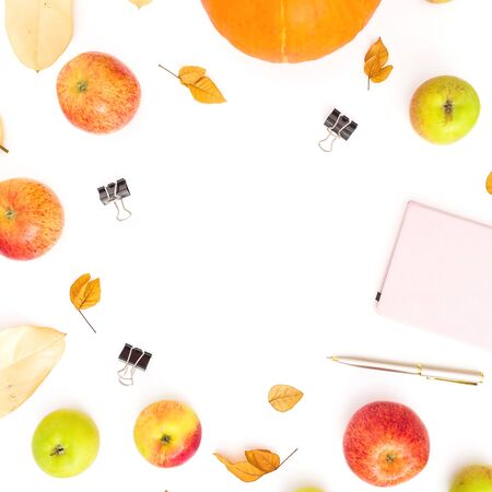 Autumn composition of fall leaves, apple and pumpkin with notebook, pen and clips on white Stok Fotoğraf