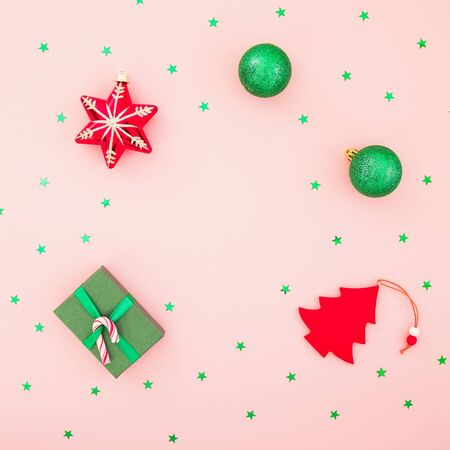 Christmas holidays. Gift box, toys and glittering green confetti on pink