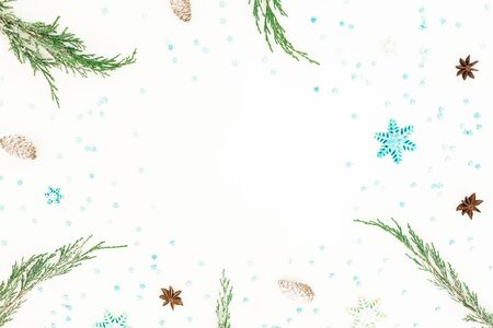 Christmas frame of evergreen tree branches, snowflakes and pine cone on white