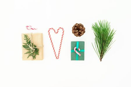 Christmas composition of gifts with candy cane, pine branch and cone on white
