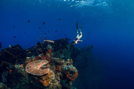 Free diver woman swimming with fins at wreck ship. Freediving in blue ocean over corals
