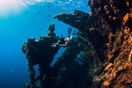 Woman free diver swim with fins at wreck ship. Freediving in ocean in wreck