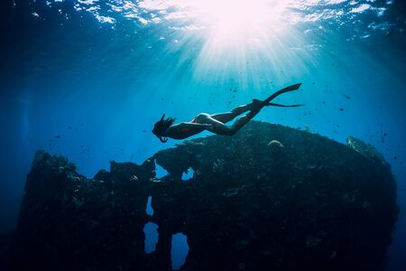 Freediver girl in pink swimwear with fins swimming underwater at wreck ship. 写真素材