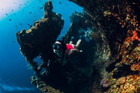 Woman free diver swim with fins at wreck ship. 写真素材