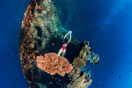 Woman free diver swimming at wreck ship. Freediving in blue ocean near wreck 写真素材