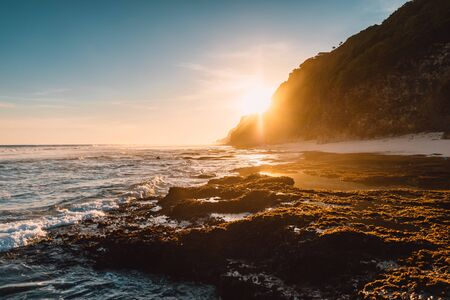 Beach with ocean waves and sunshine light at sunset or sunrise in Bali