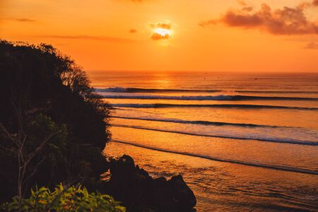 Bright warm sunset or sunrise with ocean and ideal waves for surfing