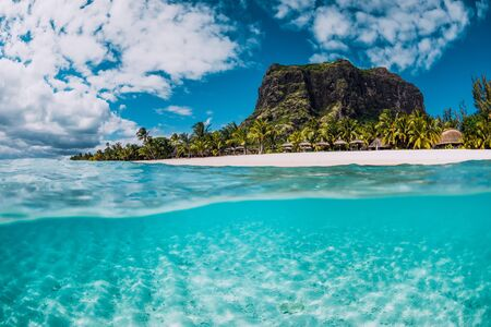 Océano de cristal tropical con la montaña Le Morne y una playa de lujo en Mauricio. Vista dividida.