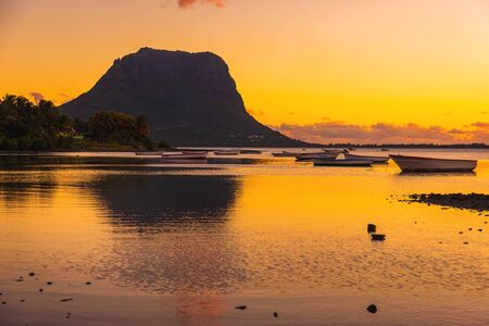 Fishing boats in ocean at sunset time. Le Morn mountain on background in Mauritius.