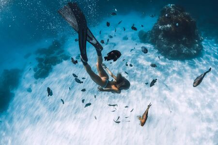Freediver girl with fins glides over sandy bottom with fishes in transparent ocean