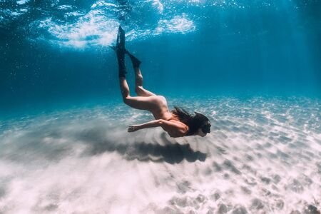 Naked woman freediver glides over sandy bottom. Beautiful woman swim with fins
