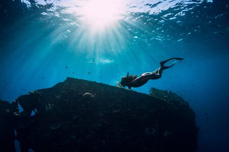 Free diver girl in pink swimwear with fins swimming underwater at wreck ship. Freediving in the ocean Stockfoto