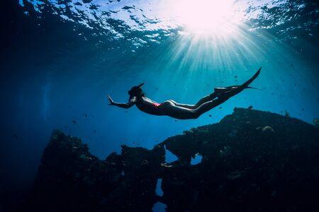 Ragazza subaquea in costume da bagno rosa con pinne che nuotano sott'acqua al relitto della nave. Apnea nell'oceano