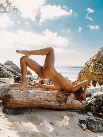 Attractive young naked woman posing at tropical beach with ocean.
