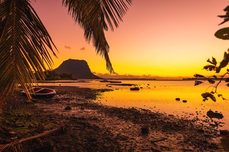 Fishing boats in a quiet ocean at sunset time. Le Morn mountain in Mauritius. Stock fotó